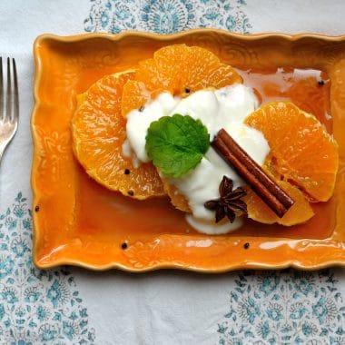 En orange tallrik med skivad apelsin med getmjölksyoghurt och två kanelstänger.