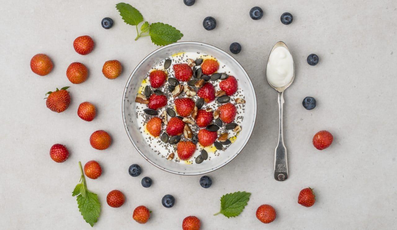 Utspridda bär och en skål med Larsa yoghurt toppad med jordgubbar, honung, chiafrön och nötter.