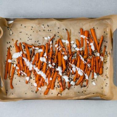 Plåt med bakplåtspapper och honungsrostade morötter med ingefära, svarta sesamfrön och vitlöksås.
