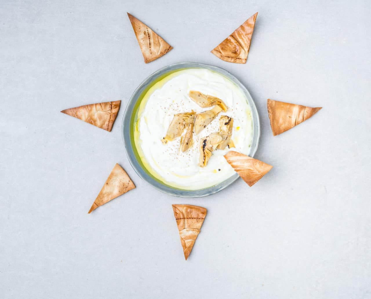 Skål med yoghurtdipp och bröd i triangelformar runt om. Toppad med kronärtskocka.