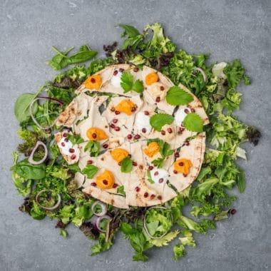 Runt plattbröd toppad med Larsa hummus, och granatöppelkärnor.Plattbrödet är omringat av salladsblad.