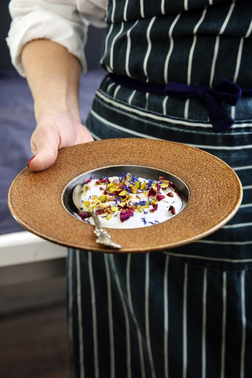 Efterrätt med larsa yoghurt och dadelsirap, toppad med pistage.