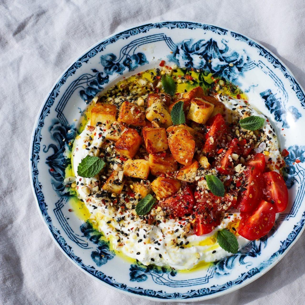 En blå och vit tallrik på en duk toppad med Halloumi bitar, Larsa yoghurt och tahini.