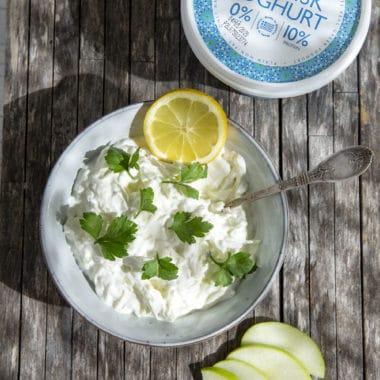 Skål med äppeltzatziki toppad med en citronskiva och dill. Äppelskivor och larsa yoghurt vid sidan om skålen.