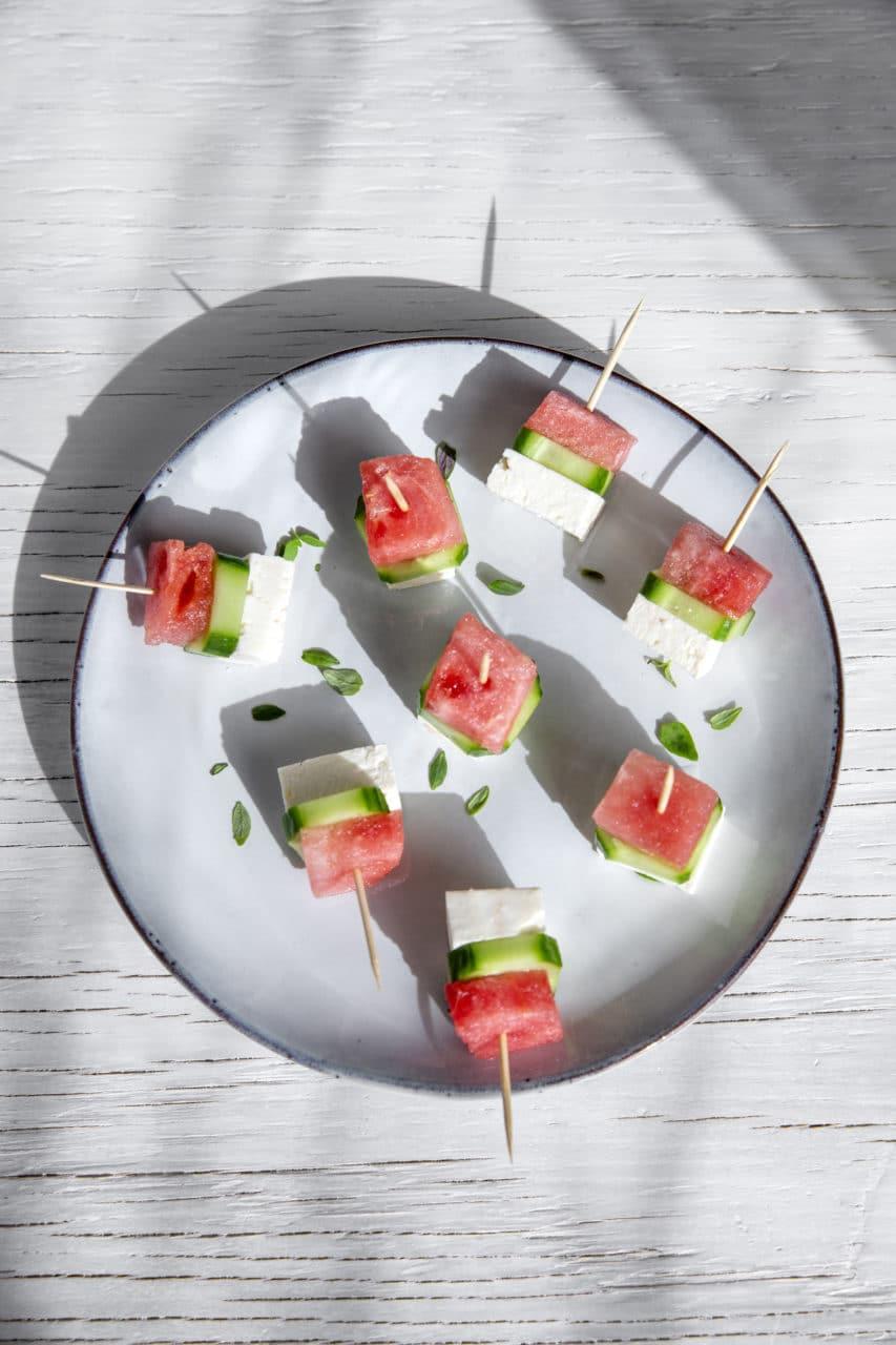En tallrik med snack, fetaost från larsa, vattenmelon och gurka på små spett.