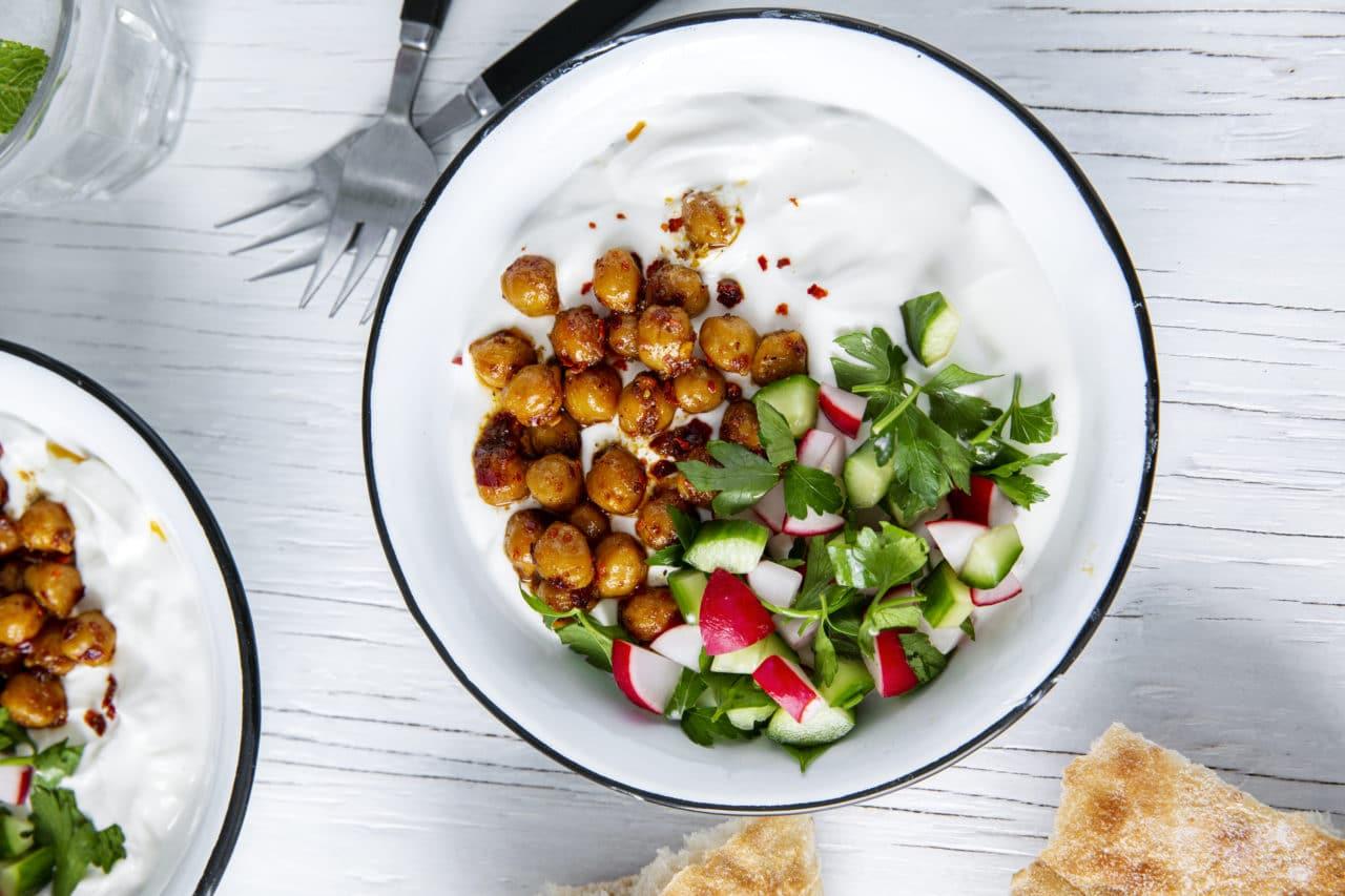 Yoghurtbowl med stekta kikärtor, rädisor och gurkhack på en rund tallrik.