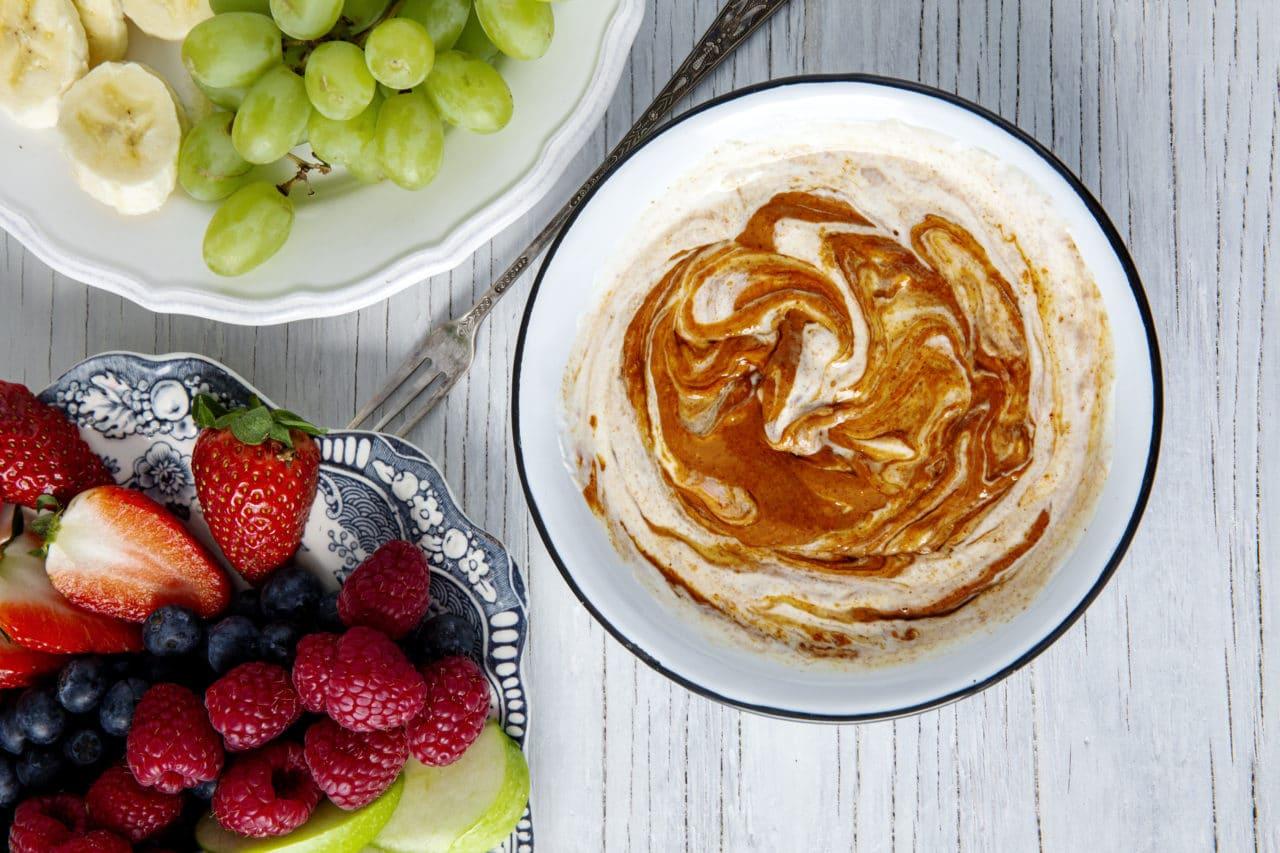 En skål med yoghurtdipp med jordnötssmör och honung. Två skålar med frukt och bär.