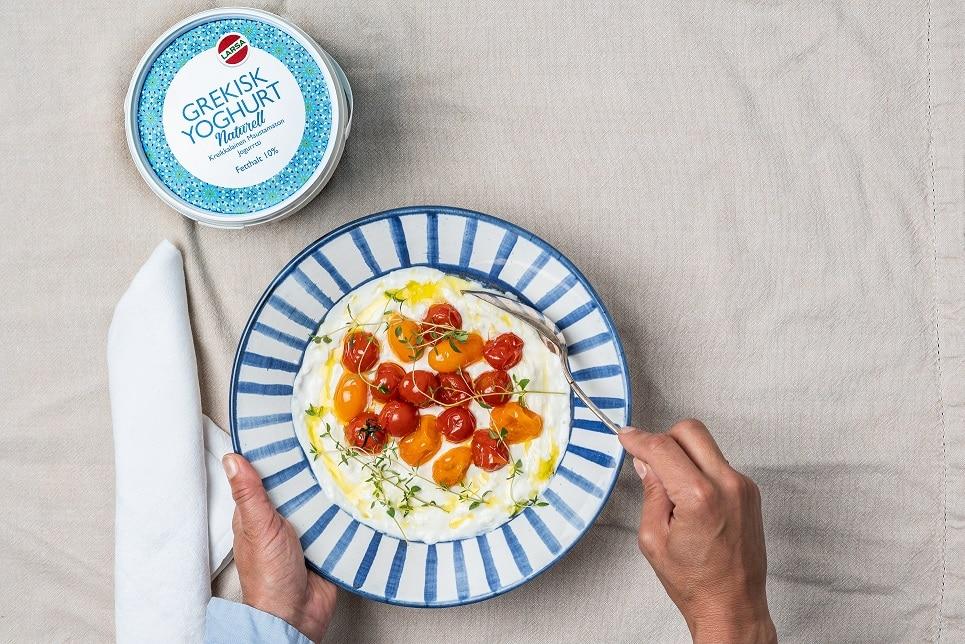 En rund tallrik med tomater med yoghurt