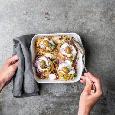 Hasselbackspotatis toppad med grekisk yoghurt, oliver och rödlök