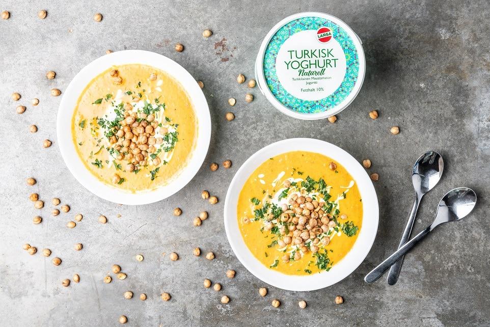 två runda tallrikar med morotssoppa med yoghurt och kikärtor på marken.