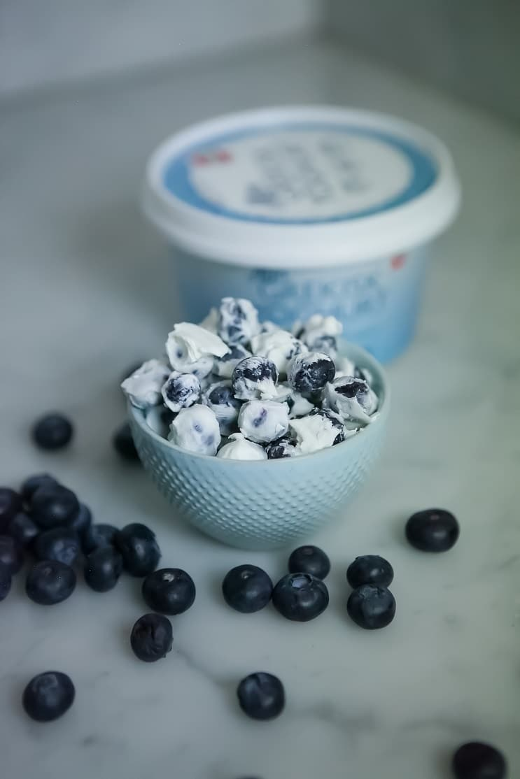 Frysta yoghurtbites. Blåbär doppade i yoghurt som ligger i en skål