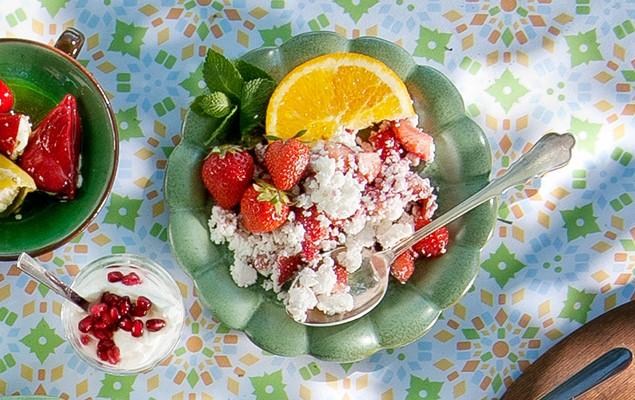 Grön skål med hela jordgubbar, smulad anari och en skiva apelsin.