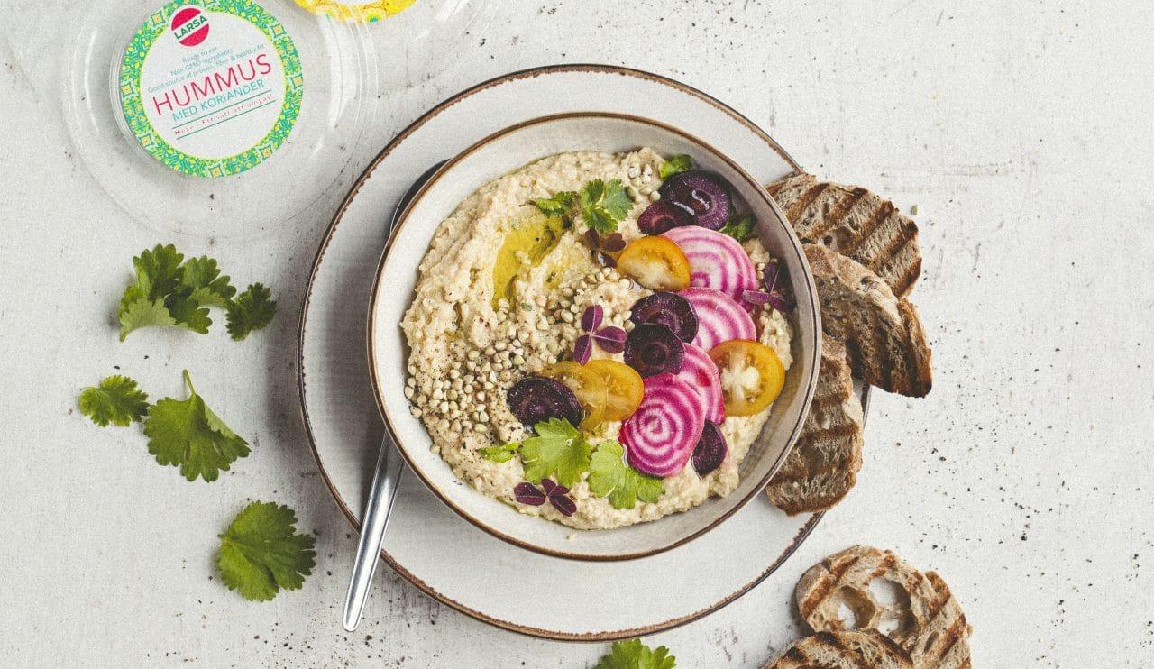 Hummus bowl och toppad med skivad rödbeta, tomat och rostade sesamfrön.