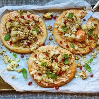 Tre runda pizzor på en bakplåt, toppad med blomkål, labneh och granatäpplekärnor.
