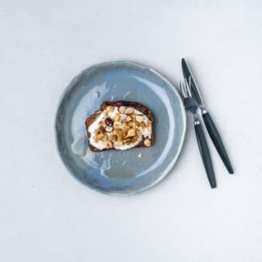 Blå tallrik med rostad macka med grekisk yoghurt toppad med nötter och honung.