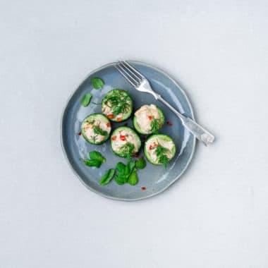 Gurkstubbar toppade med tonfiskröra och dill på en rund talltik.
