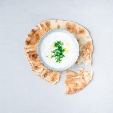 Plattbröd och en skål med klassisk tzatziki gjord på Grekisk Larsa yoghurt.