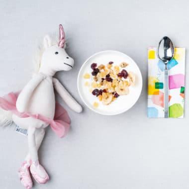 En vit och rosa leksak och ett mellanmål med larsa yoghurt toppad med nötter och torkad frukt.