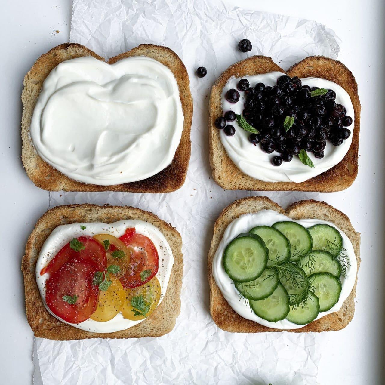 Fyra rostade bröd skivor med yoghurt som färskost. Toppad med tomater av olika fäger, blåbär och gurka.
