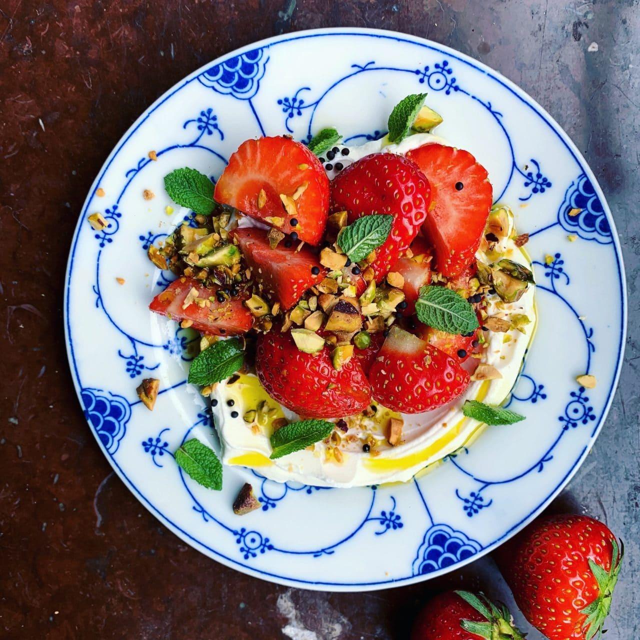 En dessert på en liten rund tallrik med Grekisk yoghurt toppat med skurna jordgubbar och finhackad pistage