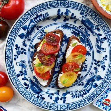 Blå och vit tallrik med rostat bröd, toppad med fetaost spread och tomater.