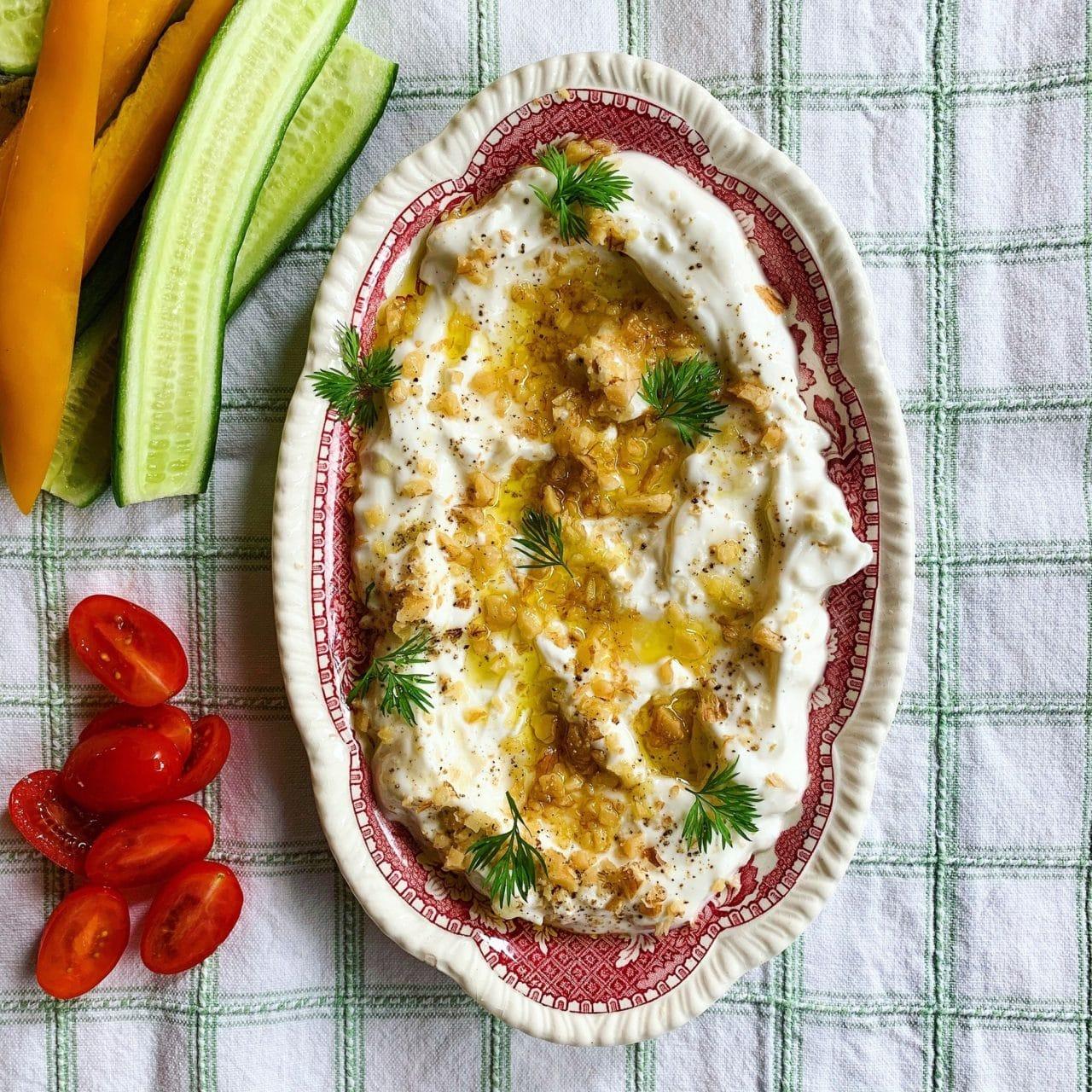 Avlång tallrik med yoghurtdipp toppad med olivolja, finhackade valnötter och dill.