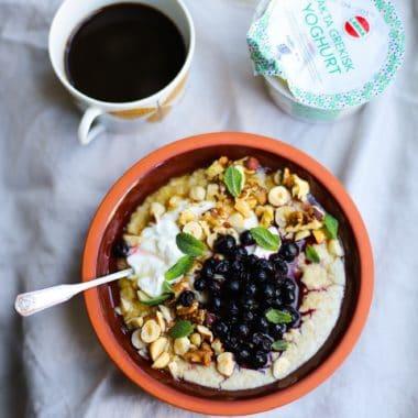 En kopp med svart kaffe och en skål med gröt toppad med Larsa yoghurt, blåbär, rostade hasselnötter och myntblad.
