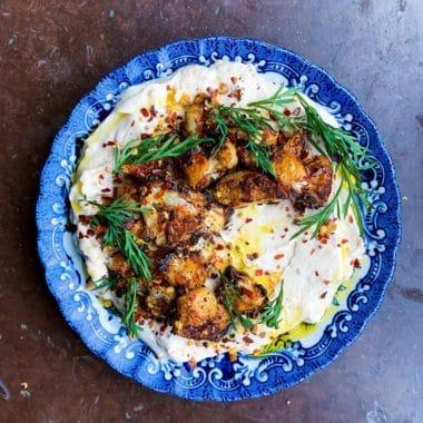 Rund tallrik med labnehkram toppad med rostad blomkål, chiliflakes och dill.
