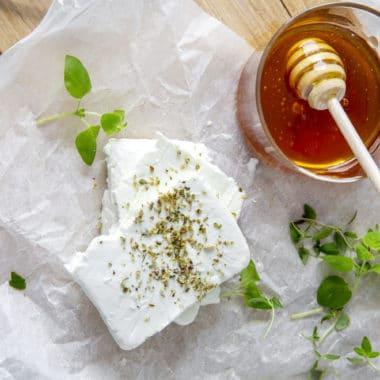 Skärbräda och bakplåtspapper, på ligger en delad feta och en skål med honung.