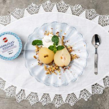 Bakade päron som ligger över en klick yoghurtgrädde