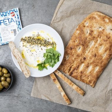 Bröd och en skål med feta dipp och oliver
