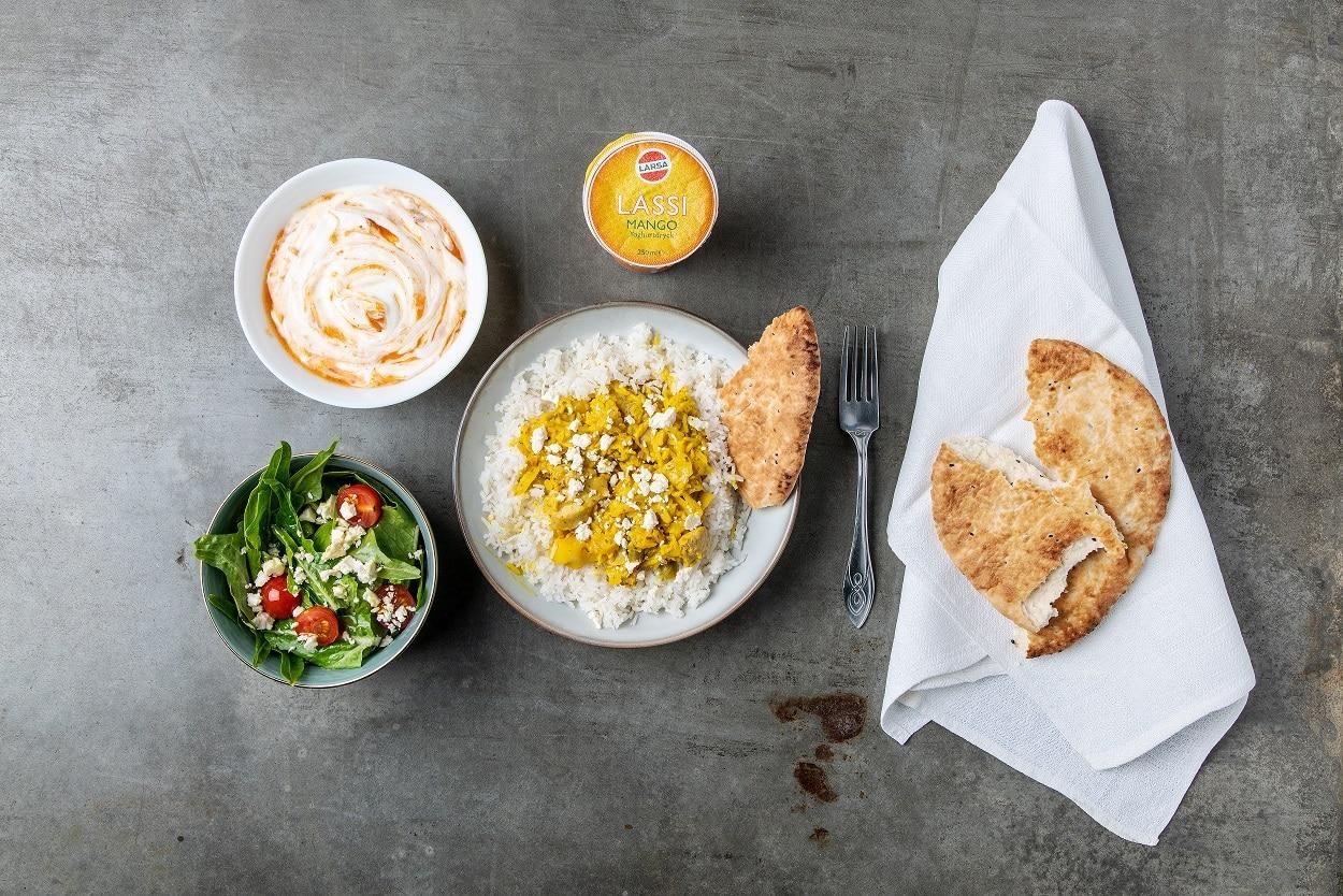 Indiskkycklinggryta med ris. En skål med sallad och en yoghurt. En servett med bröd på.