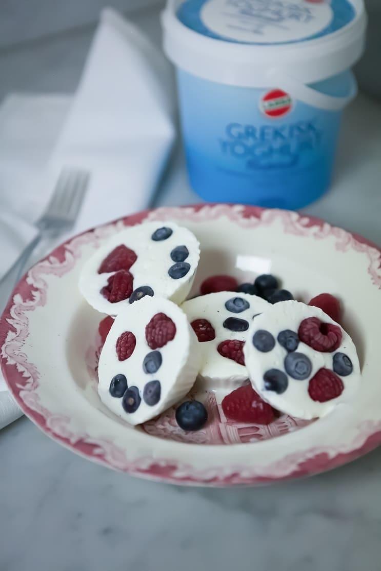 Frozen yoghurtbites med bär som ligger i en djup tallrik