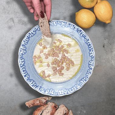 Böndippa med yoghurt, en hand som doppar ett bröd i dippen, tre citron vid sidan om.