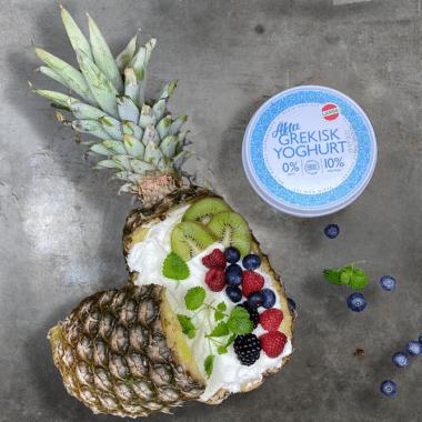 En delad fylld ananas med yoghurt och bär.