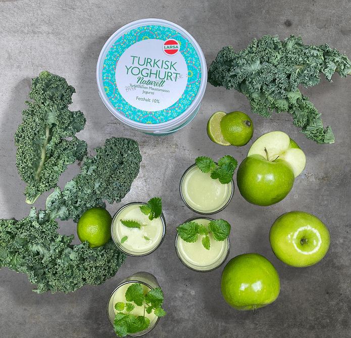 Grön smoothie i glas. Äpplen ligger utspridda över golvet tillsammans med grönkål