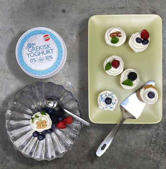 Yoghurtfrosting på muffinsar som är toppade med bär och strössel.